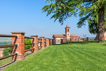 Brick fence along green lawn as small parish church on background under blue sky in Piedmont, Northern Italy. Stock Photo