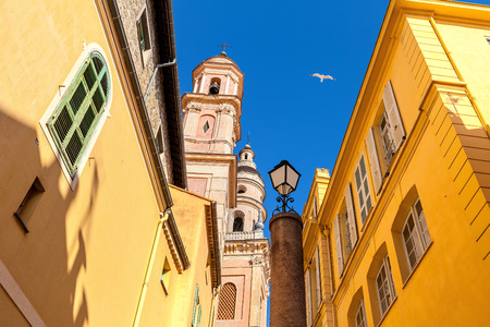 menton: Belfry of Saint-Michel Archange basilica among colorful houses under blu sky in old town of Menton, France.