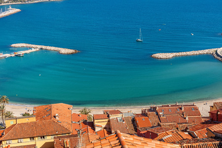 menton: Red roofs overlooking shoreline and blue water of Mediterranean sea in Menton, France.