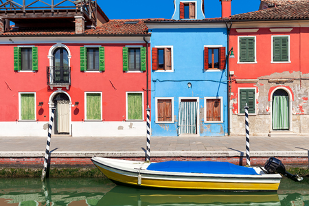 Boat on small canal in front of old colorful houses on Burano island in Italy. Stock Photo