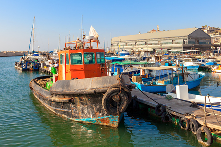 yaffo: Old colorful rust fisherman boat tied to a pier in port of old Jaffa in Israel. Stock Photo