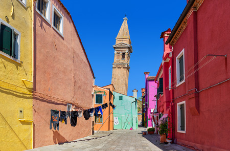 Small courtyard among colorful houses and leaning belfry on background under blue sky on Burano island, Italy. Stock Photo