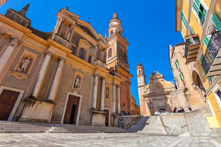 menton: Small town square and Saint-Michel Archange Basilica under blue sky in Menton, France.