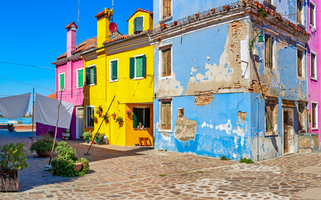 surrounded: Small courtyard surrounded by old colorful houses on Burano island in Venice, Italy.