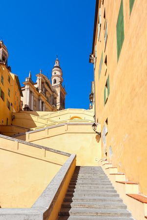 menton: Stairs among colorful walls towards Saint-Michel Archange Basilica under blue sky in Menton, France (vertical composition). Stock Photo
