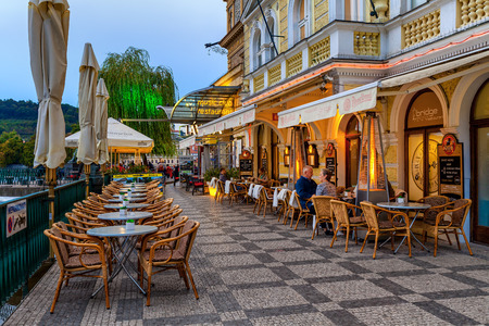 annually: PRAGUE, CZECH REPUBLIC - SEPTEMBER 22, 2015: People sitting on restaurant terrace in Prague - capital and largest city of Bohemia, fifth most visited in Europe with more than 6.4 million international visitors annually.