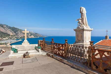 tombstones: Statue and tomb with cross at old cemetery with view on Mediterranean sea in Menton, France. Stock Photo