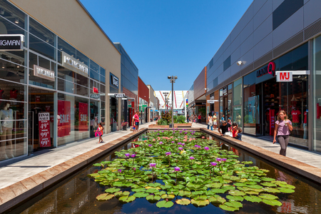 ashdod: ASHDOD, ISRAEL - JULY 24, 2015: Artificial pond with flowers among shops, boutiques and contemorary stores in openair mall - owned by BIG Shopping Centers Ltd., founded in 1994 and operates in four countries - Israel, the United States, India and Serbia. Editorial