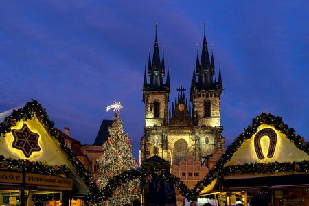 PRAGUE, CZECH REPUBLIC - DECEMBER 10, 2016: Illuminated stalls, decorated Xmas Tree and Tyn Church under evening sky during famous traditional Christmas market taking place each year in december in Old Town of Prague.