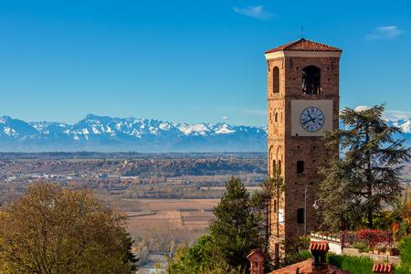 Old belfry overlooking autumnal landscape as mountain ridge on background under blue sky in Piedmont, Northern Italy. Foto de archivo