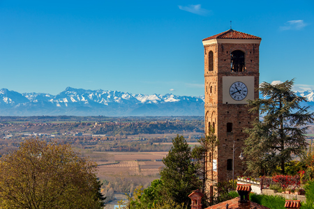 Old belfry overlooking autumnal landscape as mountain ridge on background under blue sky in Piedmont, Northern Italy. Banque d'images