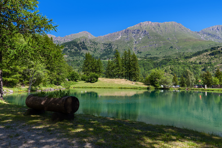 Small alpine Lake Laux surrounded by green trees and mountains in Piedmont, Northern Italy.