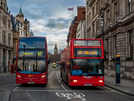 LONDON, UK - JANUARY 12, 2016: Two red modern buses on the street of London - capital and most populous city of United Kingdom, popular tourist destination.