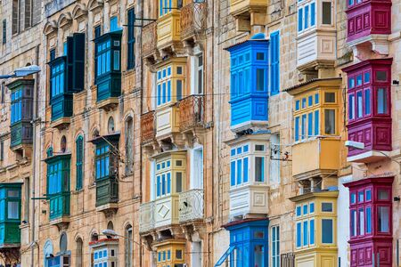 Residential building with traditional colorful wooden balconies in Valletta, Malta.