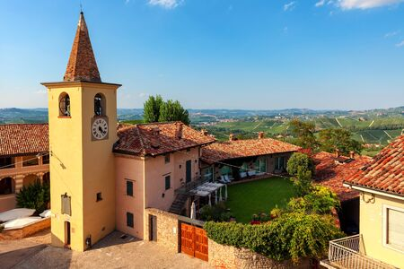 View of small parish church, rural houses and green vineyards on the hills on background under blue sky in Piedmont, Northern Italy.
