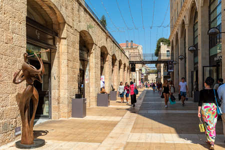 JERUSALEM, ISRAEL - JULY 16, 2017: People walking among shops, boutiques and modern art sculptures at open-air Mamilla mall - shopping street in Jerusalem, with 610 m pedestrian promenade called Alrov Mamilla Avenue, 140 stores, restaurants and cafes. Banco de Imagens - 144730441