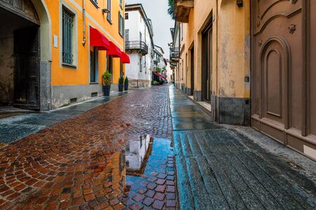 Puddle on narrow wet cobblestone street among old houses on town of Alba, Piedmont, Northern Italy.