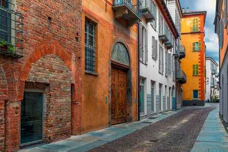 Narrow cobblestone street along colorful houses in old town of Alba, Piedmont, Northern Italy.