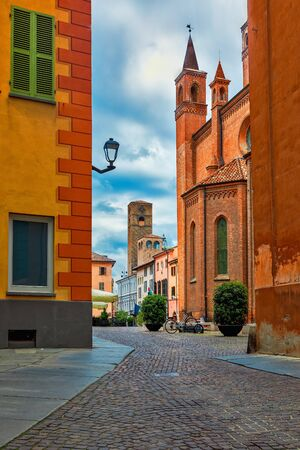 Narrow cobblestone street, San Lorenzo cathedral and medieval tower on background in old town of Alba, in Piedmont, Northern Italy. 免版税图像