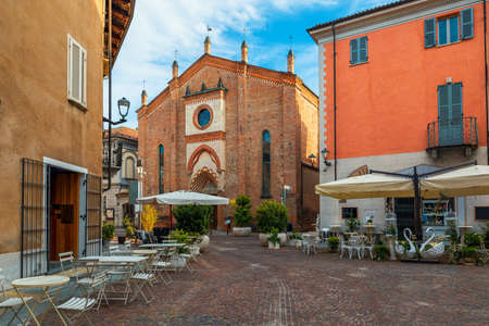 Narrow cobblestone street among old houses and San Domenico church in town of Alba in Piedmont, Northern Italy. Stock Photo