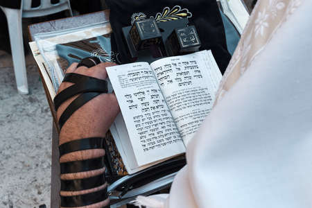 Close-up view of praying man with tefillin and torah near Western Wall in Jerusalem, Israel. Stock Photo