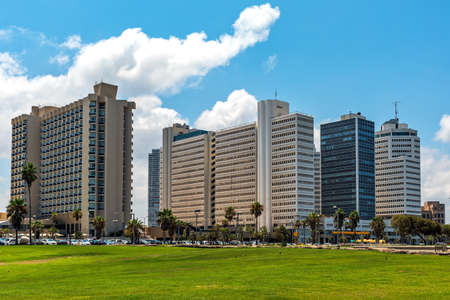 View of urban park with green grass and modern buildings on background under blue sky in Tel Aviv, Israel.