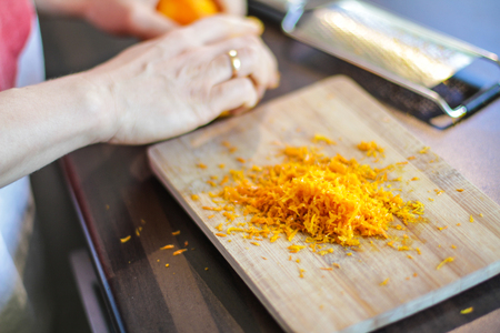 Mandarin zest on wooden board with the grater alongside