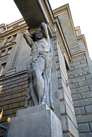 Atlas at the main entrance to the building holding portal beam, sculptural support, telamon Stock Photo