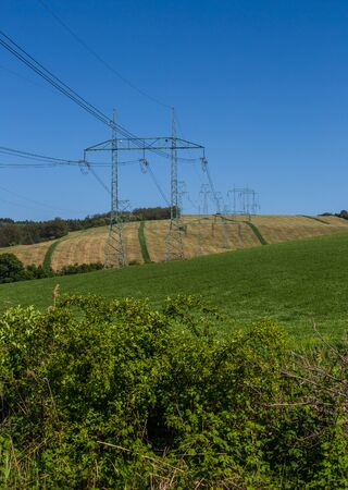 High-voltage power transmission towers over farm fields