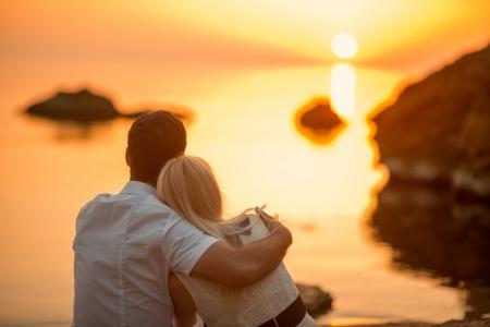 embracing couple: pareja sentada y viendo el sol en la playa al amanecer Foto de archivo