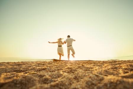 pärchen: Paar Springen auf das Meer bei Sonnenaufgang