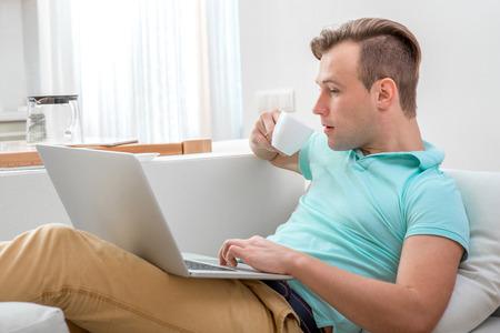 relajado: Hombre hermoso que trabaja con ordenador port�til y beber t� tirado en el sof� de su casa.