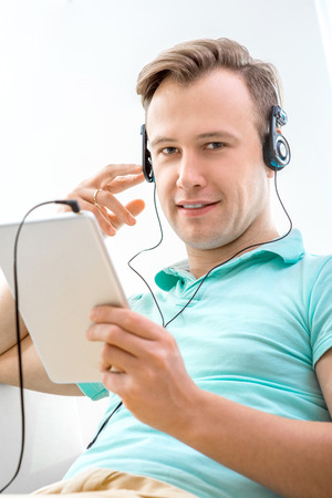 Handsome man listening to the music with tablet and headphones sitting on the couch at home photo