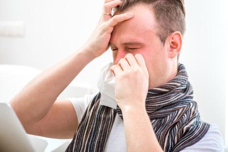 gripe: Hombre enfermo que sufre de rinitis que se sientan en el sof� de casa. Fuerte dolor de cabeza