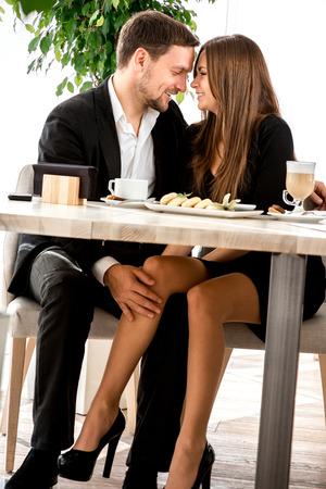 desayuno romantico: Pares jovenes que ligan con las piernas en el restaurante debajo de la mesa