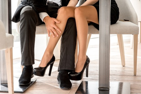 Mladý pár flirtovat s nohama v restauraci pod stolem