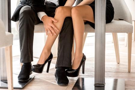 Pares jovenes que ligan con las piernas en el restaurante debajo de la mesa
