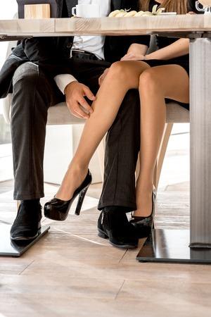 piernas hombre: Pares jovenes que ligan con las piernas en el restaurante debajo de la mesa