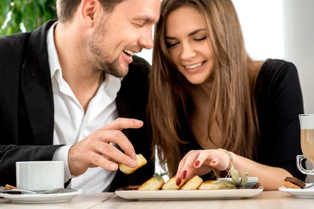 una familia comiendo: Pareja joven sonriente y comer pasteles de queso en el restaurante Foto de archivo