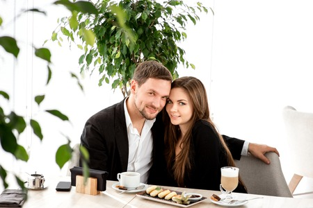 Young couple sitting and embracing at the restaurant photo