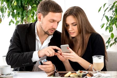 pagando: Pareja joven que paga por el tel�fono inteligente para Ther orden en el restaurante Foto de archivo