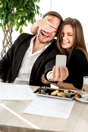 Young couple making selfie photos at the restaurant. photo