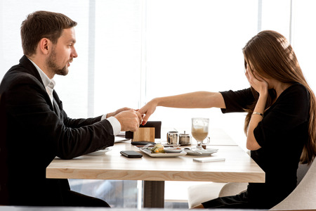 affiance: Man making proposal with the ring to his girlfriend at the restaurant. Shocked and surprised woman