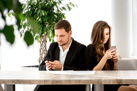 humiliated: Young couple being busy using their smart phones at the restaurant turned away from each other. Stock Photo