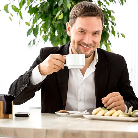 Handsome man drinking coffee at the restaurant. Business lunch. photo