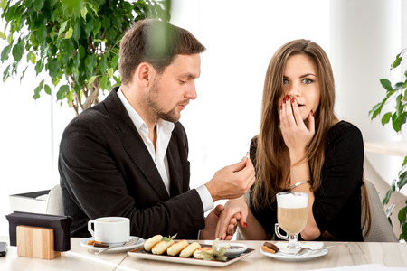 Man making proposal with the ring to his girlfriend at the restaurant. Shocked and surprised woman