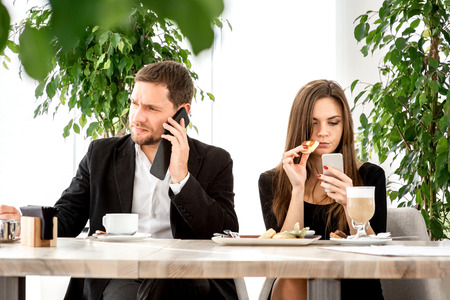 Young couple being busy using their smart phones at the restaurant photo