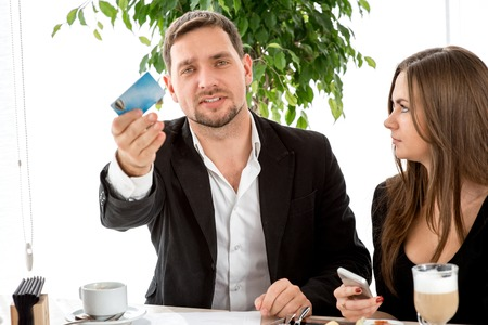 pay for: Man with credit card calling the waiter wanting to pay for the order at the restaurant