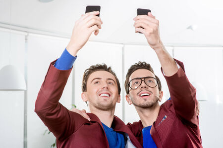 Friendly brothers twins having fun taking selfie photo with smart phone in the white home or restaurant interior photo