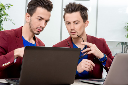 Two brothers twins in red jackets working with laptops and smart phones at the office. Family business photo